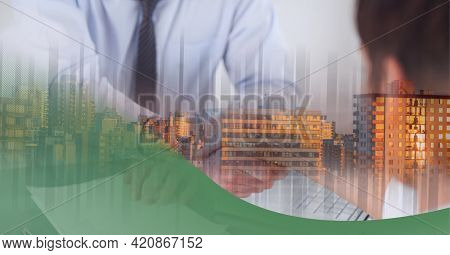Mid section of businessmen shaking hands over cityscape against green technology background. global business and technology concept
