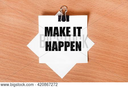 On A Wooden Table Under A Black Paper Clip Lies A Sheet Of White Paper With The Text Make It Happen