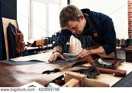 Leather Craftsmen Working Making Measupenets In Patterns At Table In Workshop Studio