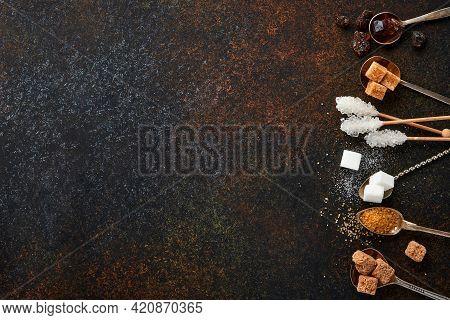 White Sugar, Cane Sugar Cubes, Caramel In Teaspoons On Dark Brown Table Concrete Background. Assorte