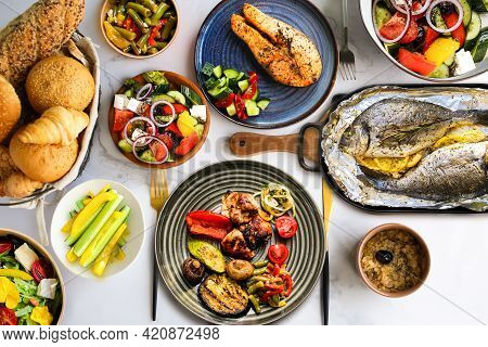 Lots Of Healthy Food On The Table. Proper Nutrition. Table With Food On Plates Top View. Healthy Foo
