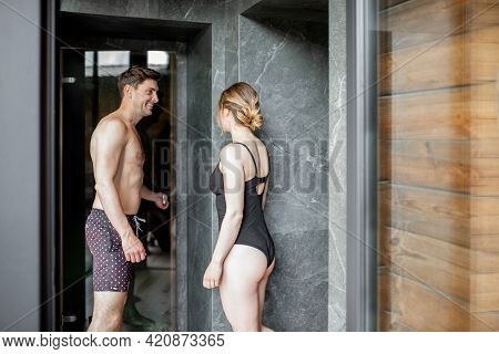 Woman Walking In Roman Sauna In Spa Complex In Black Swimsuit While Man Opens The Door And Lets The
