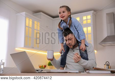 Overwhelmed Man Combining Parenting And Work At Home