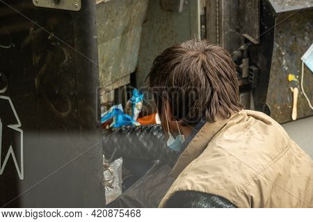 Homeless With Mask Digging In A Garbage Dumb And Looking For Plastic Or Food In Waste Container, Poo