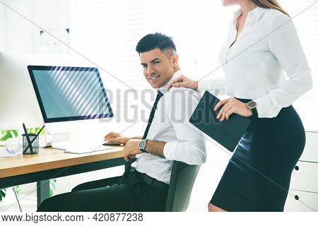 Young Woman Flirting With Her Colleague During Work In Office. Cheating Concept