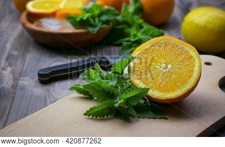 Preparation Of Summer Refreshing Fruit Drinks. Citrus And Aromatic Herbs On A Wooden Table. The Conc