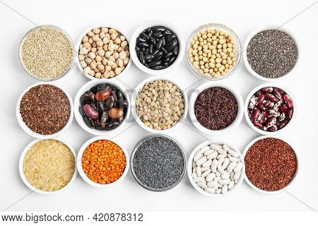 Various Raw Veggie Seeds In Bowls On White Background, Top View