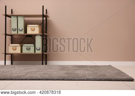 Room With Soft Grey Carpet, Shelving Rack And Pale Brown Wall. Space For Text