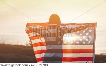 A Young Woman Holds The Us National Flag In A Field At Sunset. 4th Of July, Independence Day. Americ