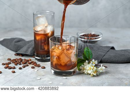 Making Iced Coffee On A Gray Background. Pouring Coffee Into A Glass With Ice. Side View.