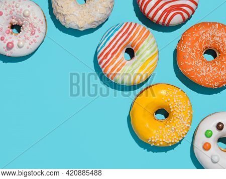 Delicious Glazed Donuts On Blue Background. Flat Lay - Set Of Different Colorful Donuts Or Doughnuts