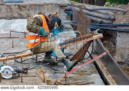 A Welder In Protective Clothing, A Helmet And Gloves Uses An Electrode To Weld Metal Beams And Iron