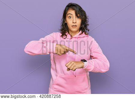 Young hispanic woman wearing casual sweatshirt in hurry pointing to watch time, impatience, upset and angry for deadline delay