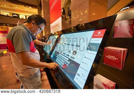 SINGAPORE - CIRCA JANUARY, 2020: man use interactive touch screen kiosk at Nge Ann City shopping center.