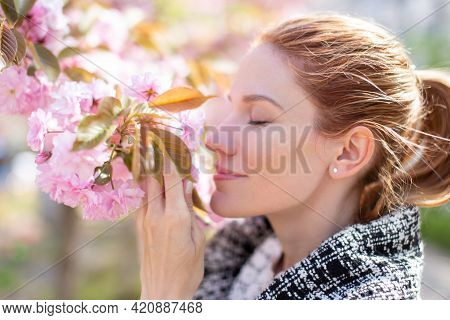 Young Positive Woman Smelling Cherry Blossom, Profile View, Eyes Closed