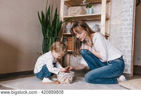 A Happy And Caring Young Mother Plays With Her Little Daughter. Happily Spend Time With Your Child