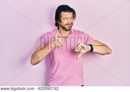 Middle age caucasian man wearing casual white t shirt doing thumbs up and down, disagreement and agreement expression. crazy conflict
