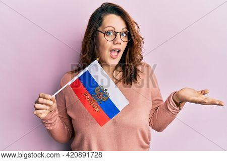 Young caucasian woman holding russia federation flag celebrating achievement with happy smile and winner expression with raised hand