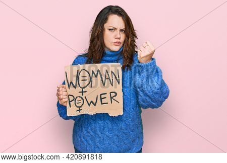 Young plus size woman holding woman power banner annoyed and frustrated shouting with anger, yelling crazy with anger and hand raised