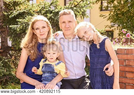 Parents With Two Little Daughters At Park. Happy Family Portrait. Nature Lifestyle. Summer Time. Cau