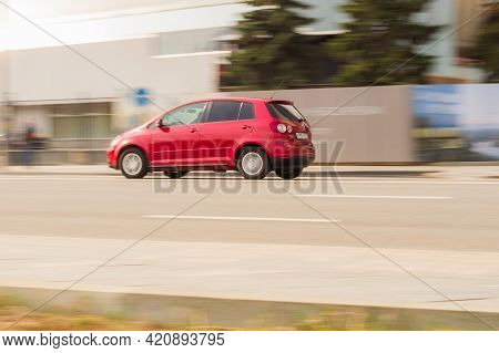 Side View Rolling Shot With Red Volkswagen Golf Plus Car In Motion. Compact Hatchback Is Driving Alo