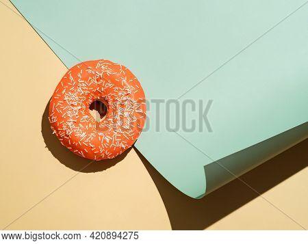 Creative Layout Made With Delicious Glazed Donut.flat Lay Orange Glazed Donut Or Doughnut On Pastel