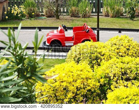 A Small Childrens Red Car Stands On A Miniature Road Surrounded By Bright Bushes. Childrens Karting