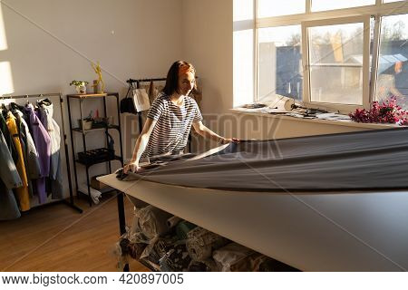 Tailor Work With Cloth At Table In Atelier. Young Fashion Clothes Designer Unrolling Fabric To Cut P
