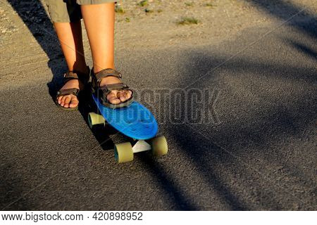 Defocus Little Urban Boy Standing On A Blue Penny Skateboard. Young Kid In The Park. City Style. Urb