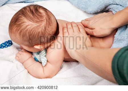 FIve month baby girl receiving massage therapy at home during lockdown. Osteopathic or chiropractic manual therapist manipulates child's back