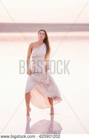 Young Blonde Woman In An Evening Airy Pastel Pink, Powdery Dress Stands Barefoot On White Crystalliz