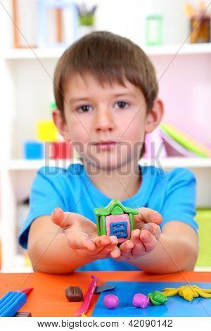 Süße kleine Junge holding-handgemachten Plastilin Pferdewagen über Schreibtisch
