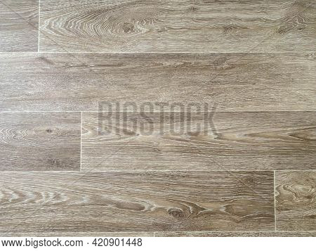 The Surface Texture Of Rubber Artificial Brown Linoleum With A Design For Wood Planks With Knots. Th