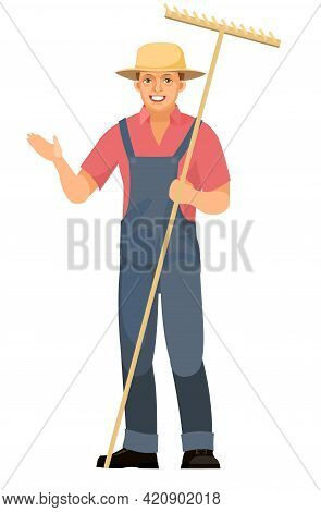 Farmer Guy Is Standing. Young Handsome Cute Boy Wearing Hat. Shows With His Hand. In Uniform, Overal