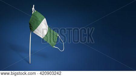 Nigeria Mask On Dark Blue Background. Waving Flag Of Nigeria Painted On Medical Mask On Pole. Concep