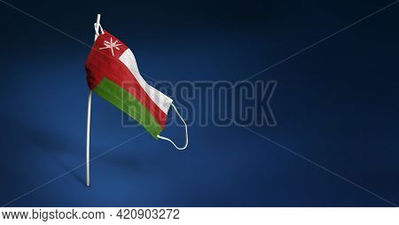 Oman Mask On Dark Blue Background. Waving Flag Of Oman Painted On Medical Mask On Pole. Concept Of T