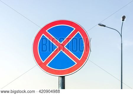 Round Road Sign With A Red Cross On A Blue Background. The Sign Indicates A Parking Ban