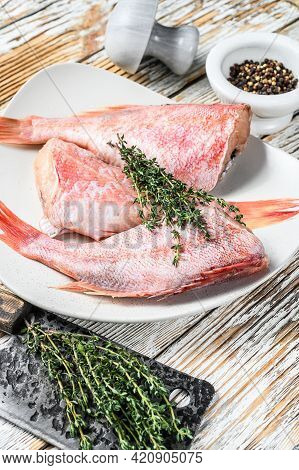 Whole Raw Red Snapper Fish On A Plate. White Wooden Background. Top View