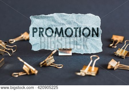 A Scrap Of Blue Paper With Clips On A Gray Background With The Text - Promotion.