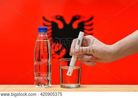 A Hand With A Water Tester Makes A Measurement In A Glass Of Clear Water Against The Background Of T