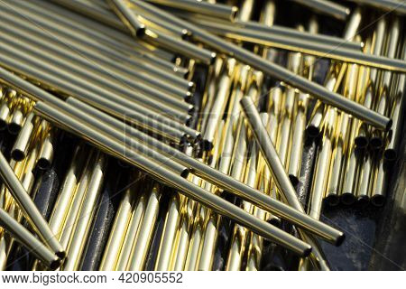 A Bunch Of Identical Brass Pipes. The Polished Brass Rods Shine In The Sun. Alloy Details.