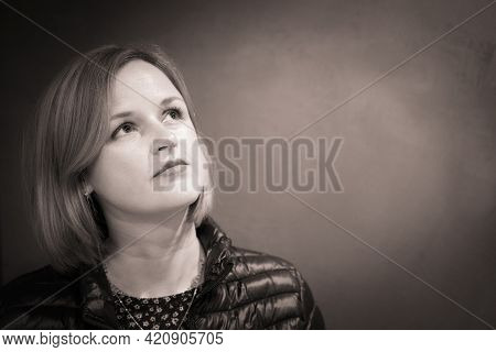 Close-up Female Portrait Looking Up Away. Adult Native Caucasian Woman Portrait. Sepia Tone Photo.