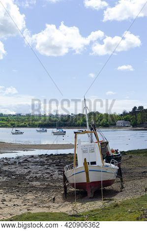 Anglesey, Red Wharf Bay. Traditional Fishing Boat Moored On Sand Flats At Low Tide. Beautiful Seasca