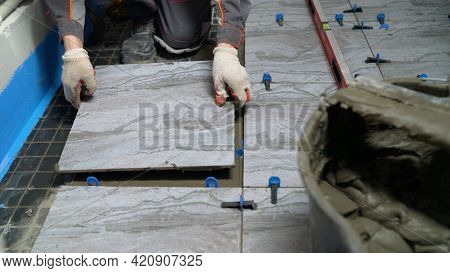 The Process Of Laying Ceramic Tiles On Glue-smeared Floors. Workers Hands With Tiles Close Up. Apply