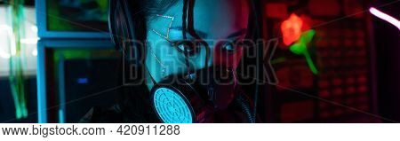 Young Asian Woman With Scar In Gas Mask And Wireless Headphones Looking Away, Banner.