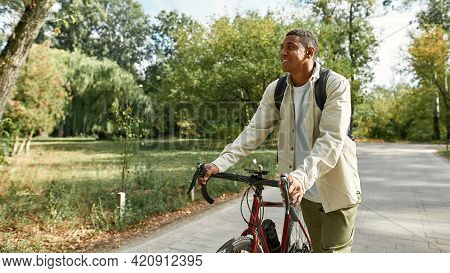 Smiling Young African American Man With Backpack Walking With Bike Along Park Alley In Spring Nature