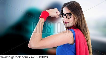 Composition of woman in glasses dressed as superhero flexing muscles on blurred medical background. super powers, support and healthcare services concept digitally generated image.