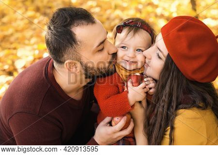 Parents Kiss Their Little Daughter On Both Cheeks While She Eats A Big Red Apple. A Warm Sunny Autum