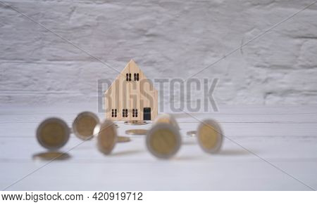 Small Wooden Houses And Coins Placed In The Corridors Represent Saving Money, Buying Houses And Land