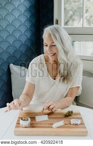 Senior woman rolling a joint